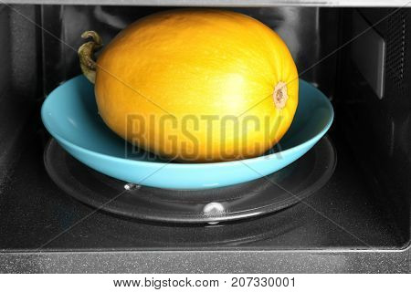 Plate with ripe spaghetti squash in microwave