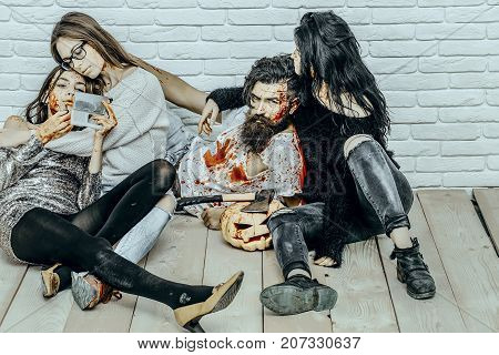 Halloween friends relaxing on wooden floor. Girl vampire applying lip gloss makeup. Halloween holiday celebration concept. Women with red blood splatters. Bearded man with bloody pumpkin and axe.