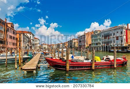 Venice old houses on Grand Canal embankment with street lamp and boats by dock. Urban landscape summer blue sky clouds. Italy.