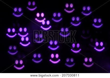 Halloween background. Smiling spooky ghost faces in the dark. Halloween concept with purple smiling ghosts bokeh. Blurrred Halloween bokeh background