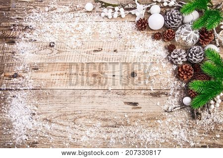 Christmas festive background with pinecone balls. Holiday greeting card branch old wooden board rustic style, copyspace and top view.