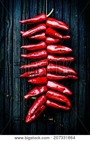 String of Espelette peppers hanging to dry on a wooden door