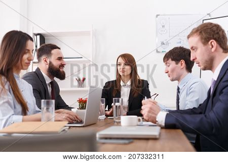 Manager with employees meeting, multiethnic, successful team with female boss. Office discussion, communication with partners at the desk