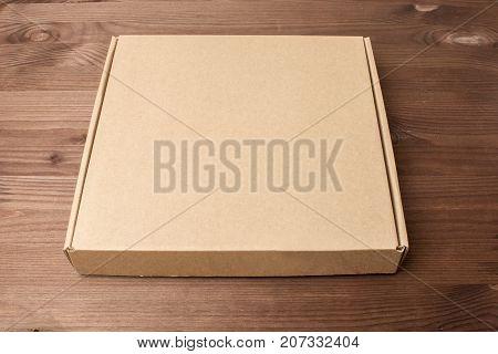 Cardboard box on a dark wooden background. Corrugated cardboard