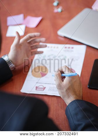 Men's hands write a new work plan for documentation in the office on a wooden brown table. Close-up of hands. Copy space. Business concept.