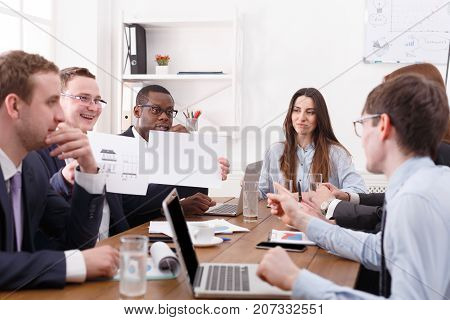Manager with employees meeting, successful multiethnic team with female boss. Employees look at the data. Office discussion, communication with partners at the desk