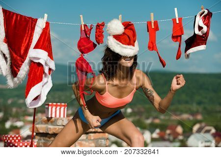 Xmas red costume on rope with pin. New year girl on sunny blue sky. Santa claus girl hanging clothes for drying. Laundry and dry cleaning. Christmas woman with happy face outdoor.