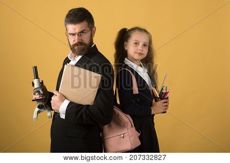 Teacher and schoolgirl with proud faces on orange background. Girl and man in suit and school uniform. Kid and tutor hold microscope book and stationery. Classroom and alternative education concept