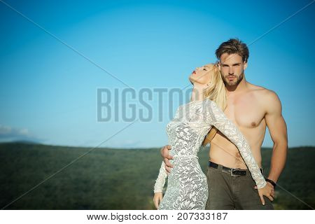 Man or macho with naked torso in jeans. Woman or girl with long blond hair in lace dress. Couple in love on blue sky. Fashion and beauty. Relationship heterosexual and lifestyle concept copy space