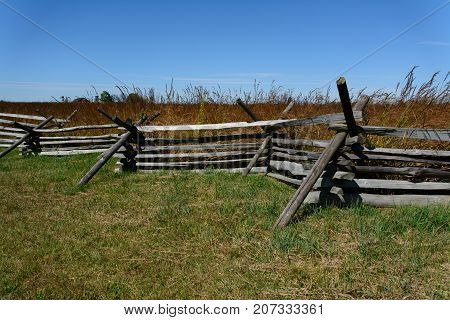 A split rail fence borders a field of wild grasses with a clear blue sky in Gettysburg, Pennsylvania, USA.