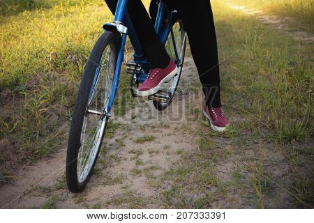 A human is sitting on a bicycle. Legs. Nature
