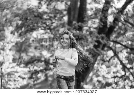 Pretty school age girl brunette with happpy smiling face running in autumn forest on background of trees with yellow leaves