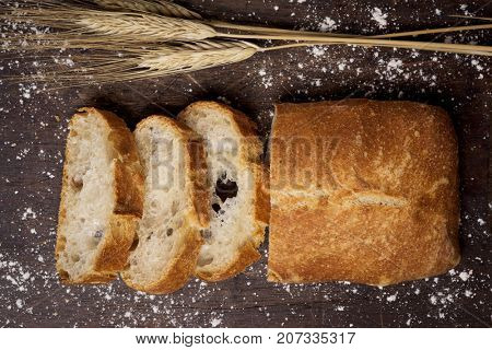 high-angle shot of some slices of pa de vidre or pa de coca, a bread typical of Catalonia, Spain, on a rustic wooden table