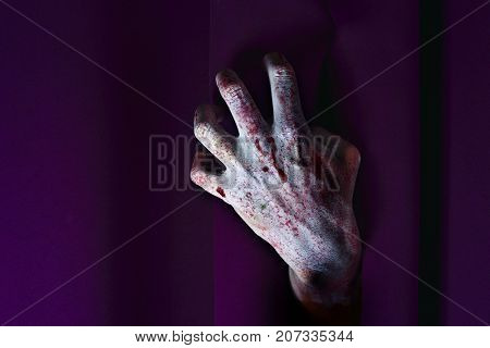 closeup of the scary hand of an undead man coming out from behind a purple stage curtain