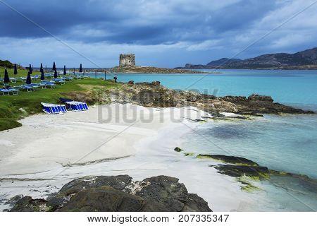 a view of the Spiaggia della Pelosa beach in Sardinia, Italy, with the Torre della Pelosa tower and the Isola Piana island in the background