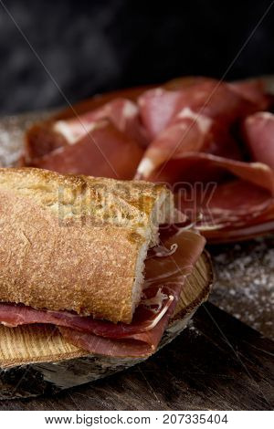 closeup of a typical spanish bocadillo de jamon, a serrano ham sandwich, on a rustic wooden table, next to a plate with some slices of serrano ham poster