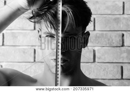 Guy With Builders Ruler Near Brick Wall. Worker With Roulette