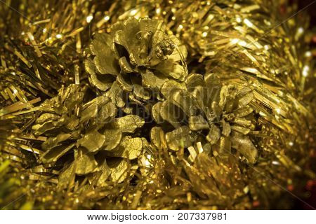 New Year's and Christmas toys - decoration of bumps on the background of a gold festive tinsel
