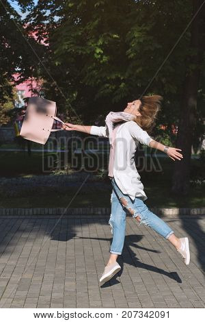 Jumping happy free woman in jeans with leather handbag outdoor. Easiness happiness concept.