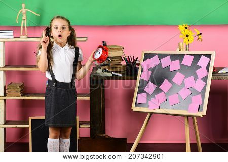 Schoolgirl With Surprised Face Having Idea Holds Red Clock