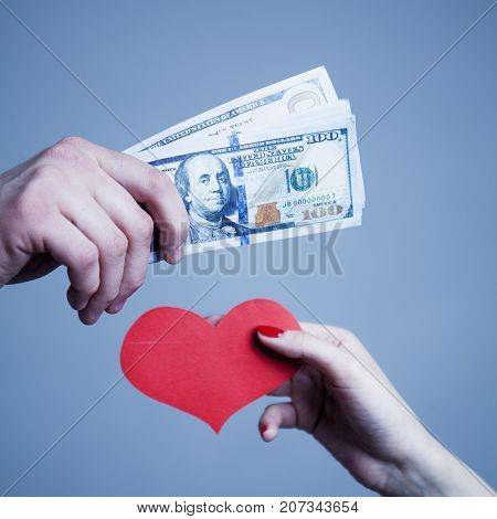 Love for money. Money over love. Man is paying for sex in Dollar banknotes. Escort and prostitution concept.