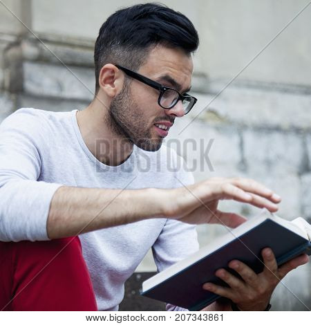 Young man with book of knowledge. Handsome male student with beard reading book. (Knowledge education development concept)