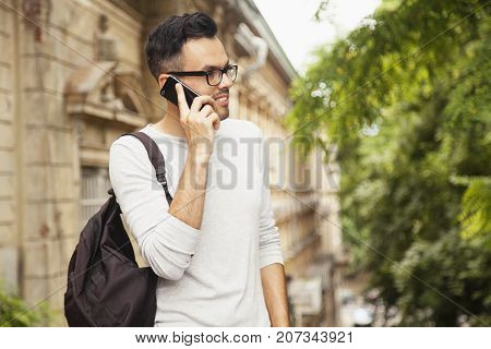 Young excited happy male tourist with a backpack talking with friend on phone in old European town (communication tourism vacation holiday concept)