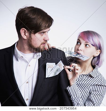 Woman takes money from her husband. Humorous picture. (Gender inequality wealth family budget concept)