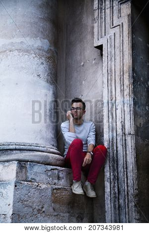 Young male tourist talking with friend on phone in old European town (communication tourism vacation holiday concept)