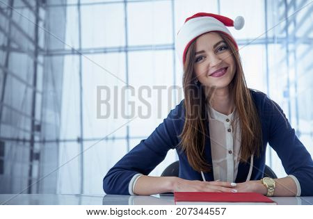 Funny Laughing Christmas girl with red fluffy Santa Hat in office (New Year Christmas holidays businesswoman concept)