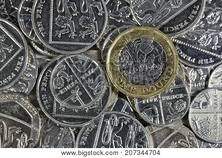 One pound coin over a pile of silver five and ten pence coins with copy space