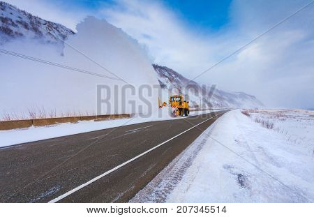 Snowplow truck (Snow removal truck) is removing the snow from the highway during a cold snowstorm winter day