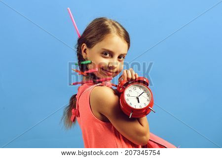 Kid In Pink Dress With Colored Pencils Holds Alarm Clock