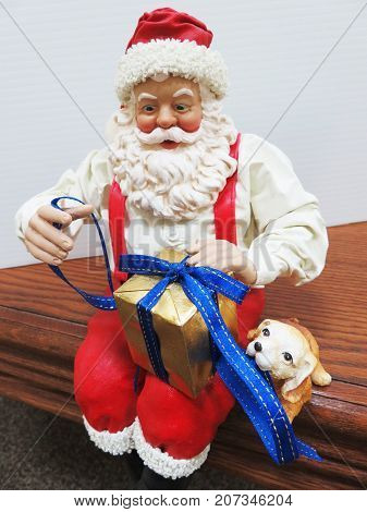 Fabric maché Santa with white shirt and suspenders, sitting on table wrapping gift, puppy at his side