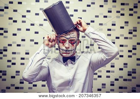 Portrait of Man on Halloween. The face of dead man in black hat. Halloween concept. Scary mask for Halloween. Joker face