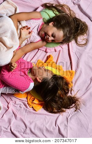 Girls Lie On White And Pink Bed Sheets Background Tickling