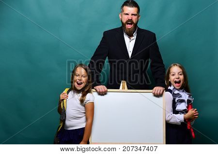 Girls And Man With Happy Faces. Schoolgirls Near Marker Board