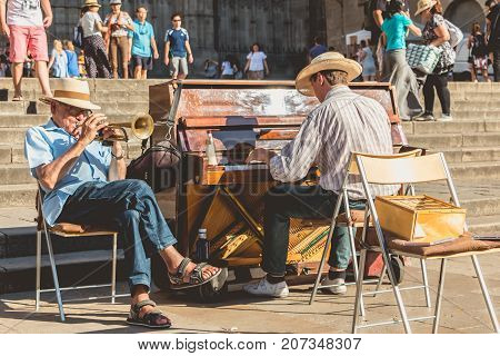 Pianist And Trumpet Player Plays For Tourists In Front Of The  Cathedral Of Barcelona