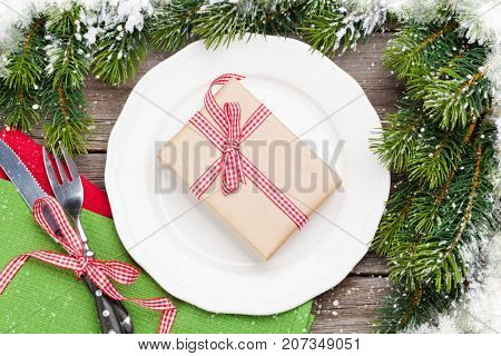 Christmas gift box over dinner plate, silverware, fir tree. Top view