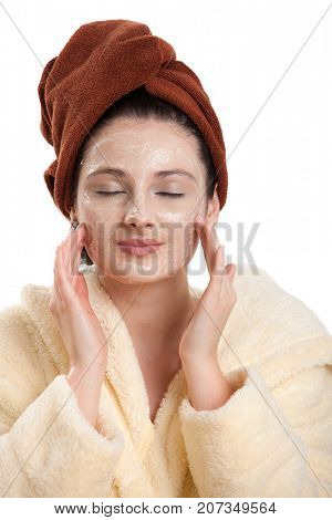 Attractive teenager girl wearing bathrobe, hair wrapped in towel, applying cream, eyes closed, smiling. Isolated on white.