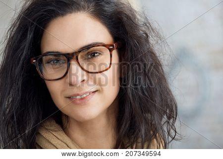 Closeup portrait of attractive caucasian woman in glasses, smiling.