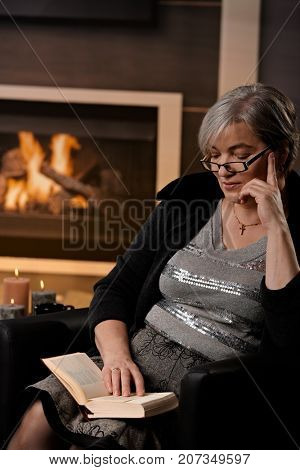 Mature woman sitting at fireplace on a winter day. reading book.