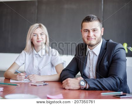 Beautiful blonde and attractive man sitting side by side and posing for working project in the office. Grey wall on the background. Business concept.