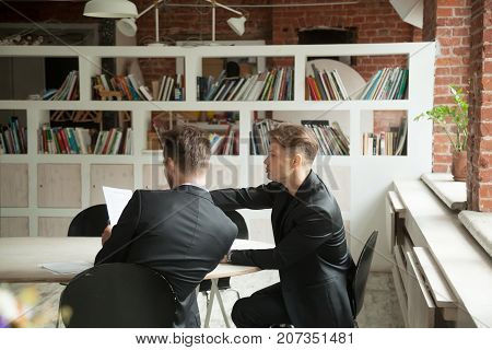 Two young male executive coworkers looking at marketing plan document. Project manager and CEO discuss new contract deal, planning new business project. Teamwork, coworking and collaboration concept.