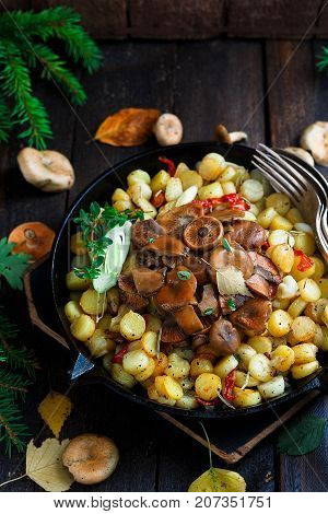 Saffron milk cap mushrooms with fried potatoes, rustic style, top view