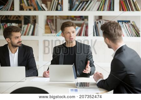 Young serious boss in front of laptop consulting two male employees during briefing meeting. Executive employee talking about company goals to coworkers. Manager sharing important corporate news.