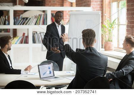 Employee raises hand to ask business coach a question during briefing. African american CEO consulting team of coworkers about new project, improvements in company workflow. Corporate meeting concept.