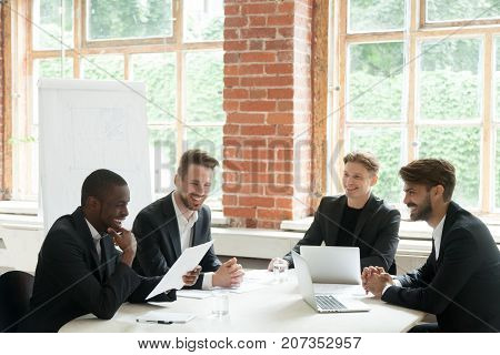Group of multiethnic cheerful smiling businessmen during briefing meeting. Employees talking about company positive goal outcome, coworkers happy to share good news about rising financial profit.