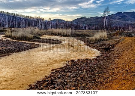 Yellow river with red - yellow acid stones. Yellow tinted river by copper on the ground. Water used in life study for life detection in Mars. Post-industrial landscape