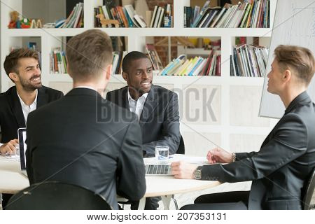 Multiethnic team of male coworkers discussing corporate plans during briefing. Businessmen having discussion about investment opportunities, company goals to improve workflow and financial profit.